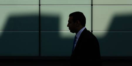 Silhouette of a banker walking in the shadows.