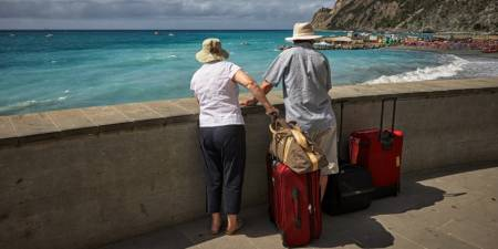 An elderly couple standing by the sea with suitcases.